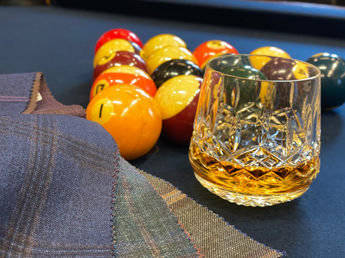 Fabric samples on pool table with pool table balls and glass of whiskey